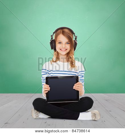 music, technology, people and childhood concept - happy girl with headphones showing tablet pc computer blank screen over green chalk board background