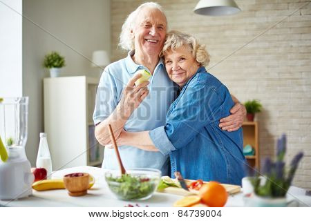 Affectionate seniors in embrace looking at camera