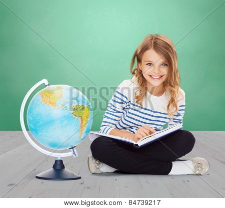 education, geography, childhood, people and school concept - little student girl studying with globe and book over green chalk board background