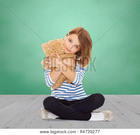 childhood, school, toys and people concept - cute little student girl hugging teddy bear over green chalk board background