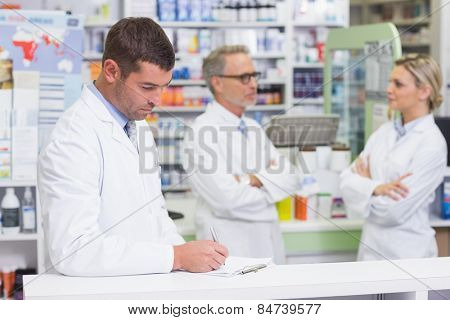 Pharmacist in lab coat writing a prescription in the pharmacy