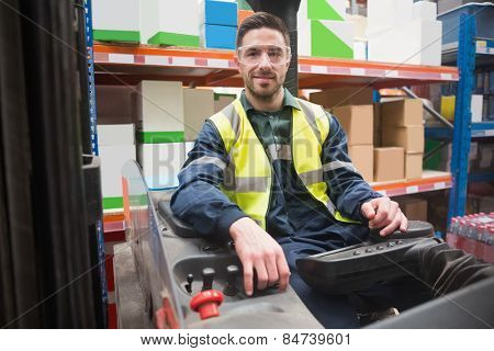Smiling driver operating forklift machine in warehouse