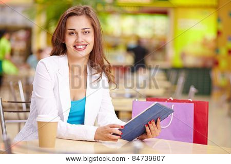 Attractive shopper looking at camera during rest after shopping