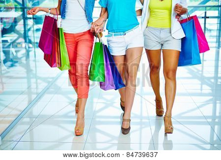 Legs of three consumers with paperbags walking down trade center