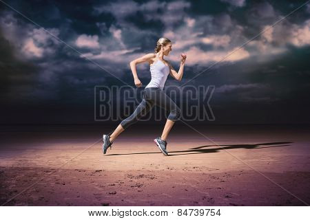 Pretty fit blonde jogging against dark cloudy sky