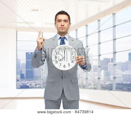 business, people, time management and gesture concept - businessman in suit holding clock showing 8 o'clock and pointing finger up over office room and window with city view background
