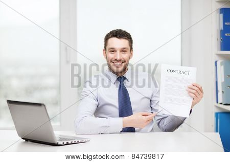 business, office and technology concept - smiling businessman with laptop computer and contract at office