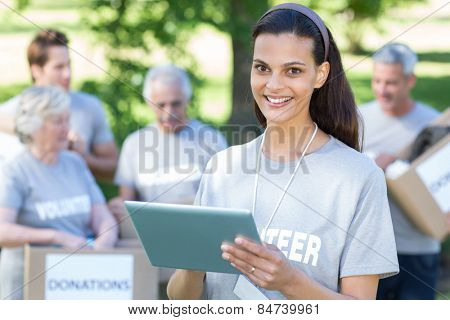 Smiling volunteer brunette using tablet pc on a sunny day