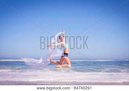 Fit woman jumping gracefully on the beach with scarf against fitness interface