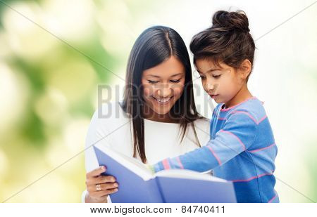 family, children, education, school and happy people concept - happy mother and daughter reading book over green background
