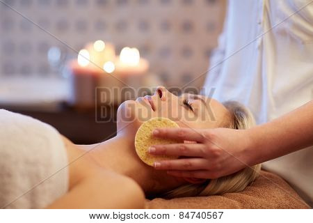 people, beauty, spa, healthy lifestyle and relaxation concept - close up of beautiful young woman lying with closed eyes and having face massage with sponge in spa