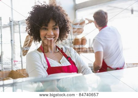 Pretty waitress posing with arms crossed at the bakery