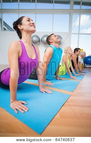 Happy fit people doing the cobra pose in fitness studio