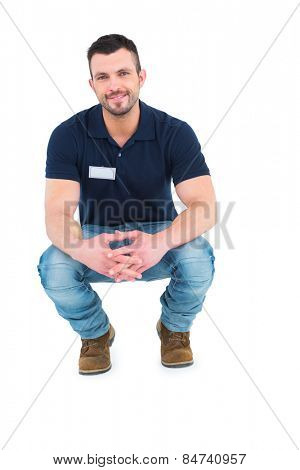 Handyman crouching on white background