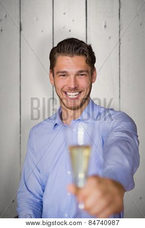 Man offering champagne against white wood