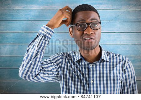 Young businessman thinking scratching head against wooden planks