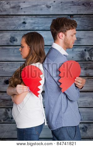 Side view of young couple holding broken heart against wooden background in blue