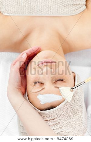 Relaxed Young Woman Receiving White Cream On Her Face