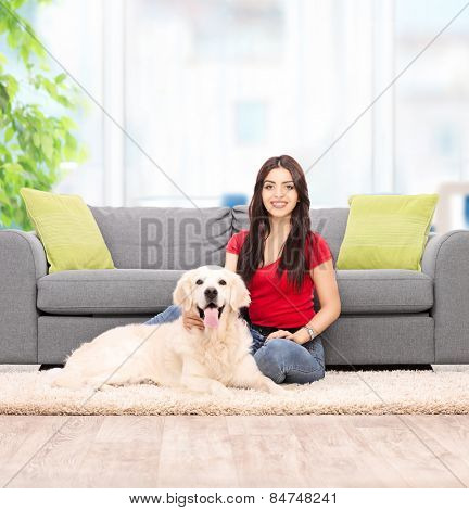 Young woman sitting by a sofa with her dog at home shot with tilt and shift lens