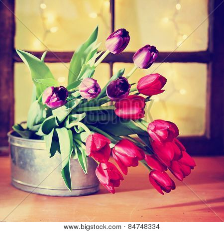 tulips on a wooden board in front of a window pane with bokeh toned with a retro vintage instagram filter app