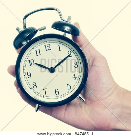 closeup of the hand of a man holding a mechanical alarm clock, with a retro effect