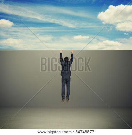 man in formal wear climbing up on grey wall