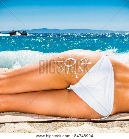 Hot beautiful woman with suntan loton sign in bikini lying on the beach. Greece.