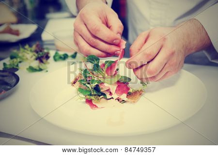 Chef is making fish appetizer on restaurant kitchen, toned image