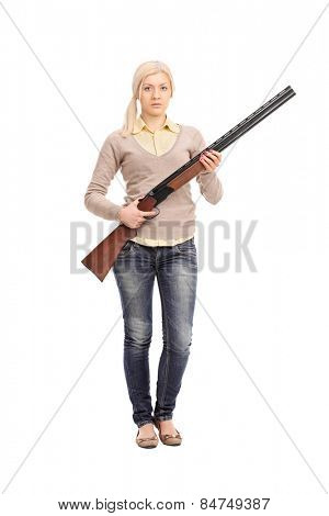 Full length portrait of a serious girl holding a shotgun isolated on white background