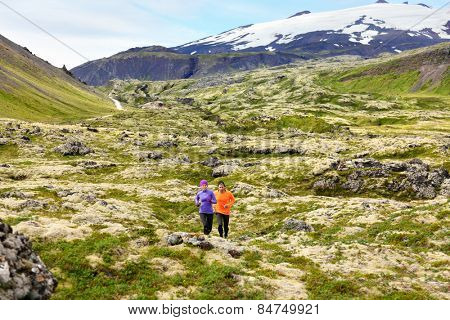 Running sport. Runners on cross country trail run outdoors working out for marathon. Fit young fitness model man and asian woman training together outside in mountain nature on Snaefellsnes, Iceland.