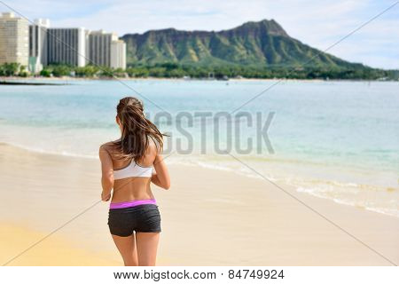 Running woman runner jogging on beach run. Female athlete fitness runner jogger training living healthy active exercise lifestyle exercising outdoor on Waikiki Beach, Honolulu, Oahu, Hawaii, USA.