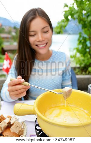Cheese fondue - woman eating local Swiss food dipping bread in melted cheese. People eating traditional food from Switzerland having fun by lake in the Alps on travel in Europe.