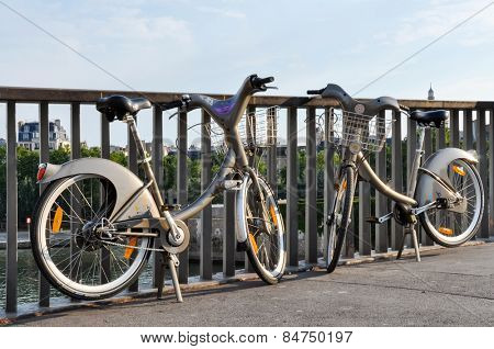 PARIS, FRANCE - CIRCA AUGUST 2009: Two Velib' on a bridge on the river Seine. Velib' is a public bicycle sharing scheme