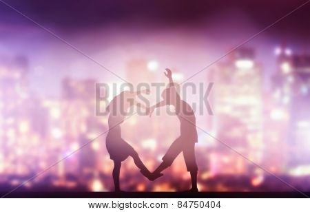 Happy couple in love making heart shape. City at night background.