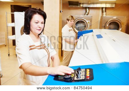 Hotel linen cleaning services. Woman with ironing machine working