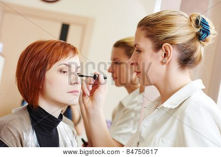 Makeup technique. mascara eyelashes of redheaded woman in beauty salon