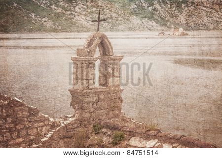 The old church overlooking the sea in bad weather in retro style. Montenegro