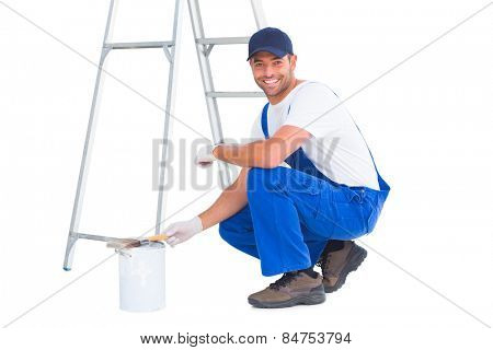 Full length portrait of happy handyman crouching by paint can on white background