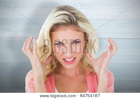 Pretty young blonde feeling angry against bleached wooden planks background