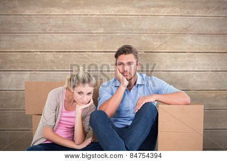 Unhappy young couple sitting beside moving boxes against wooden surface with planks