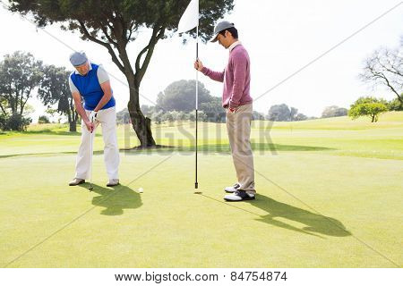Golfer swinging his club with friend at the golf course
