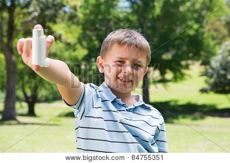 Little boy showing his inhaler on a sunny day