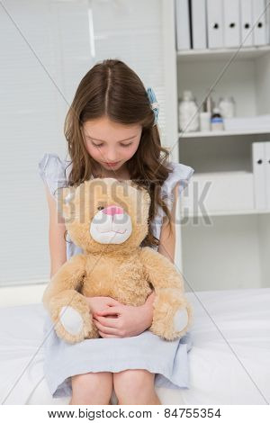 Little girl with her teddy bear in her harms in medical office