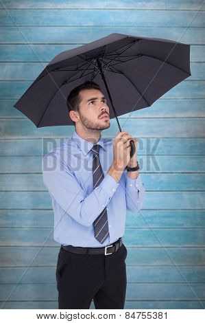 Anxious businessman sheltering with umbrella against wooden planks