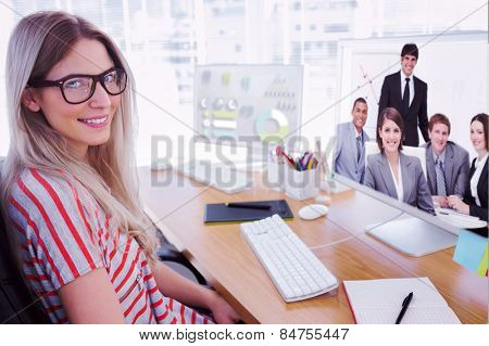 Attractive photo editor working on computer against happy business group having a meeting