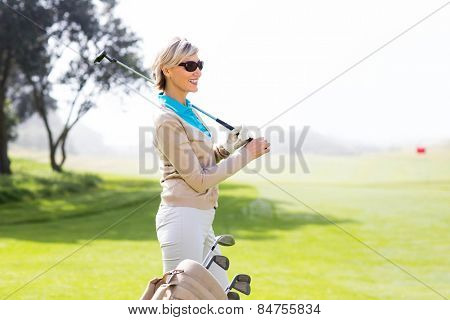Cheerful golfer smiling on a sunny day at the golf course