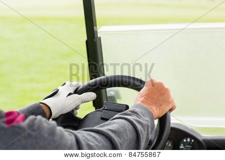 Golfer driving his golf buggy forward on a sunny day at the golf course