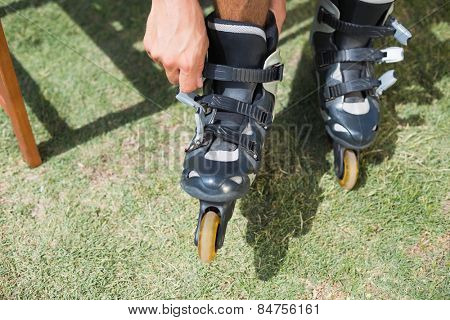 Man putting on his roller blades on a sunny day