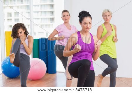 Sporty women practicing kickboxing at fitness studio