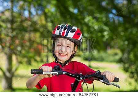 Happy little boy on his bike on a sunny day